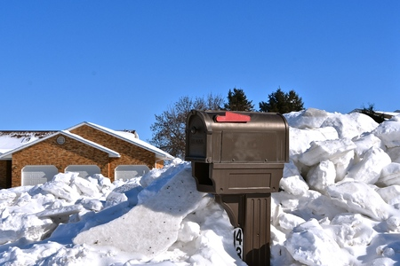 A mailbox is nearly buried with chunks of snow removed from a driveway after a winter snowstorm.