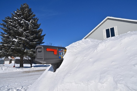 A mailbox is buried in a snowdrift and nearly hides the house is dug out enough to receive the daily mail