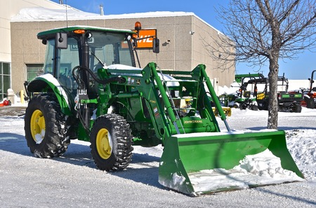 MOORHEAD, MINNESOTA, February 14, 2019: The new tractor with a snow scoop is a H240, a product of John Deere Co, an American corporation that manufactures agricultural, construction, forestry machinery, diesel engines, and drivetrains.