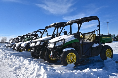 MOORHEAD, MINNESOTA, February 14, 2109: The row of snow covered Gators are products of John Deere Co, an American corporation that manufactures agricultural, construction, forestry machinery, diesel engines, and drivetrains.