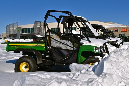 MOORHEAD, MINNESOTA, February 14, 2109: The row of snow covered Gators are products of John Deere Co, an American corporation that manufactures agricultural, construction, forestry machinery, diesel engines, and drivetrains. Publikacyjne