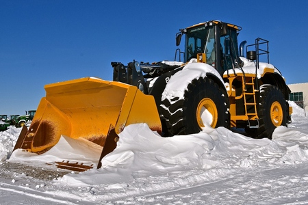 MOORHEAD, MINNESOTA, February 14, 2019: A huge 4-wheel drive tractor with a massive bucket for snow removal tractor is a product of John Deere Co, an American corporation that manufactures agricultural, construction, forestry machinery, diesel engines, a