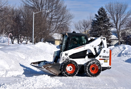 MOORHEAD, MINNESOTA, February 20, 2019: The S650 Bobcat skid steer removing driveway snow is headquartered in West Fargo, North Dakota. Editorial
