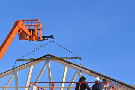 Hoists and  lifts are being used in the construction of a new industrial warehouse. Stock Photo