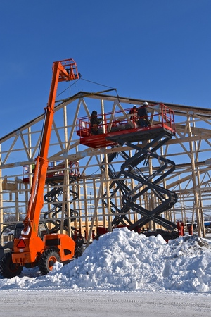 Hoists, lifts, and scissor jacks are being used in the construction of a new industrial warehouse.