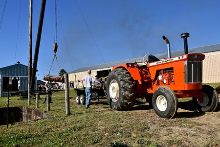 ROLLAG, MINNESOTA, September 2 ,2018: Unidentified volunteers winch logs out of the water on a boom to be delivered to a sawmill at the annual WCSTR farm threshers reunion in Rollag held each labor Day weekend where thousands attend.