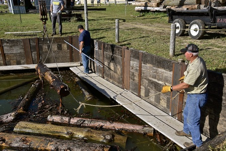 ROLLAG, MINNESOTA, September 2, 2018: Volunteer unidentified volunteers lift logs out of the water on a boom to be delivered to a sawmill at the annual WCSTR farm threshers reunion in Rollag held each labor Day weekend where thousands attend. Editorial