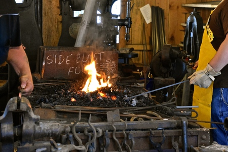 Several blacksmiths using tongs, anvil, and sledge are shaping hot molten metal in an old forge Imagens - 122832761