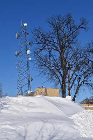 A massive snowdrift partially blocks the viewing of a large building and communications tower.