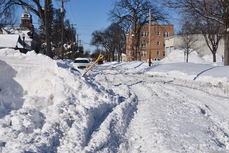 An unplowed street in a city with ruts finds ruts and tracks made by vehicles driving after a heavy snowfall.