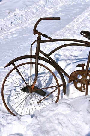 The front part of a very old bicycle throws it's shadow in the wintry snow.