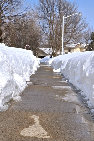 Evidence of the first melting of snow is seen with moisture on parts of a sidewalk with snowbanks on either side.