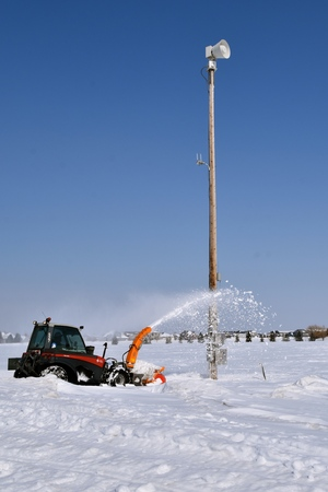 A new wood utility pole with various metal boxes controlling and measuring electrical flow is gaining accessibility with the aid of a snowblower after a snowstorm