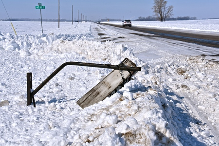 A rural mailbox on a county road has been destroyed by a snow plow after a winter snowfall.