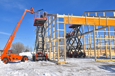 Hoists lifts, and scissor jacks are being used in the construction of a new industrial warehouse. Imagens