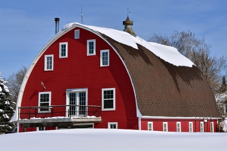 Snow on the roof of an old red rounded barn is in the first stage of melting