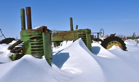 BARNESVILLE, MINNESOTA, March 11, 2019: The old John Deere tractor partially buried by snow was made from John Deere Co, an American corporation that manufactures agricultural, construction, forestry machinery, diesel engines, and drivetrains