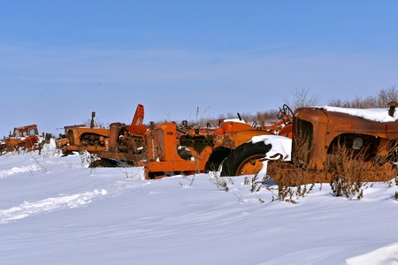 BARNESVILLE, MINNESOTA, March 11, 2019: The snow covered old orange tractors are from the company of Allis Chalmers, a manufacturer of machinery for various industries including agricultural equipment, construction, power generation, and power transmissio Editorial