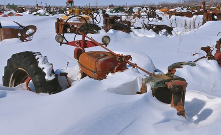 Tractors in a salvage and junkyard are buried in the deep snow after winter snowstorms.