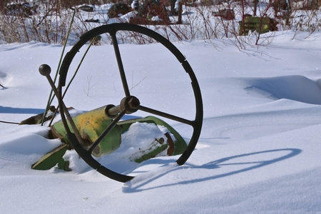 A steering wheel of an old tractor is all that is visible after a winter blizzard