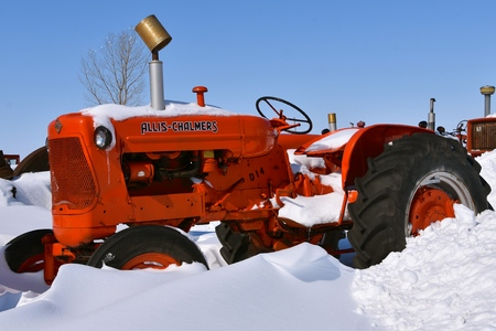BARNESVILLE, MINNESOTA, March 11, 2019: The snow and ice covered old tractor is from the company of Allis Chalmers, a manufacturer of machinery for various industries including agricultural equipment, construction, power generation, and power transmission