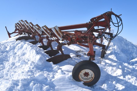 An old seven bottom plow lies on top of a huge pile of removed snow from a road through a salvage and junkyard.