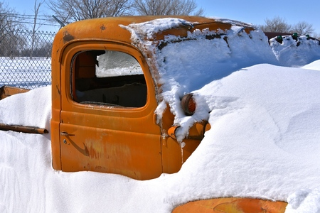 A blizzard leaves an old orange pickup buried in the deep snow Stock Photo