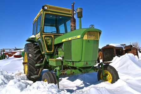 BARNESVILLE, MINNESOTA, March 11 2019: The snow covered tractor is  products of John Deere Co, an American corporation that manufactures agricultural and construction equipment, drive trains, and transmissions.