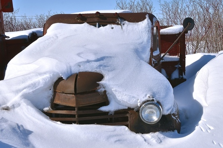 An old  rusty one ton truck is buried in the snow after a blizzard.