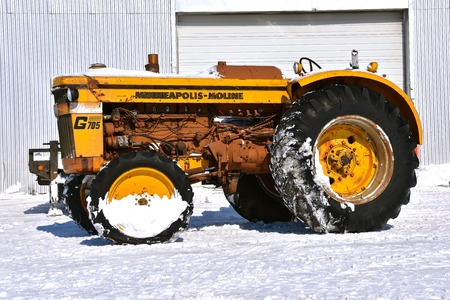BARNESVILLE, MINNESOTA, March 11 2019: The partially snow covered Minneapolis Moline tractor was produced in Hopkins, Minnesota. an American corporation that manufactures agricultural and construction equipment and is now a part of AGCO.