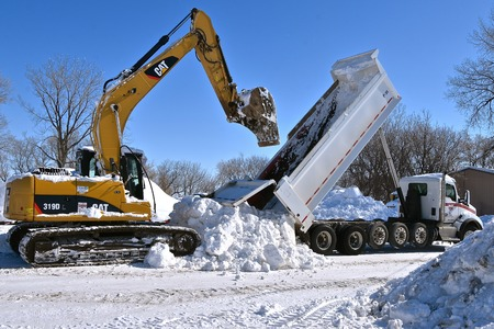 SABIN, MINNESOTA, March 11, 2019: The Cat 319D, an excavating machine removing snow from a truck box is a product rom Caterpillar Inc., an American corporation  founded in 1925 which designs, develops, manufactures, markets and sells machines.
