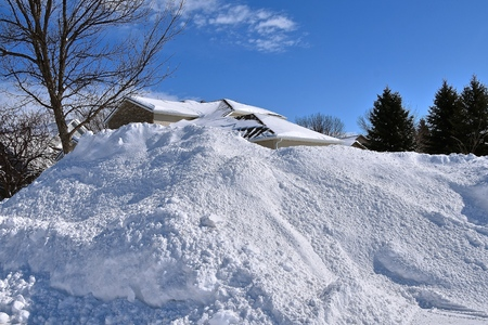 nA massive snowdrifts blocks a house from view after a blizzard.