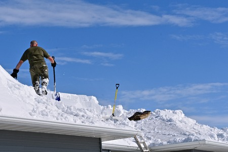 Snow is being removed from a roof with a shovel after a heavy snowfall. Stock fotó