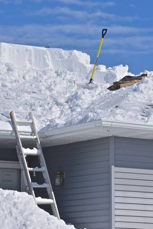 Snow is being removed from a roof with a shovel after a heavy snowfall. Stock Photo