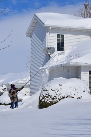Snow is being removed from a roof  with a snow rake after a heavy snowfall.