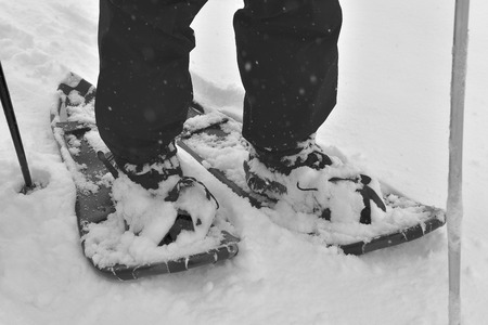 A hiker is standing on a pair of snowshoes as the snow is falling. (black and white)