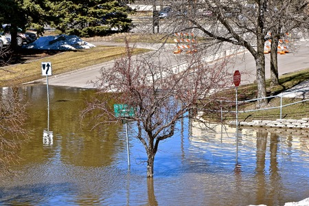 A flooded river has covered a n intersection from the melting snow during the spring thaw.