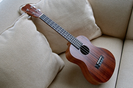 A four stringed wooden ukulele is left propped upright on a white couch