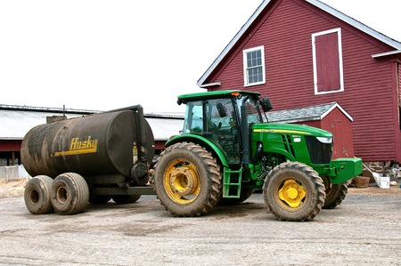 ROWLEY, MASSACHUSETTS, April 28, 2019: The 6140 John Deere tractor  pulling a Husky manure spreader is a product of John Deere Co, an American corporation that manufactures agricultural and construction equipment, drive trains, and transmission