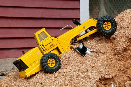 A yellow toy road grader is parker on a pile of wood shavings and sawdust.