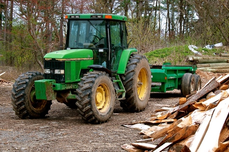 ROWLEY, MASSACHUSETTS, April 28, 2019: The  7400 John Deere tractor  pulling a trailer at a sawmill is a product of John Deere Co, an American corporation that manufactures agricultural and construction equipment, drive trains, and transmission Editorial