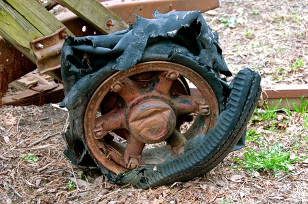 A very old rotten tire is left on a rusty rim of an old trailer.