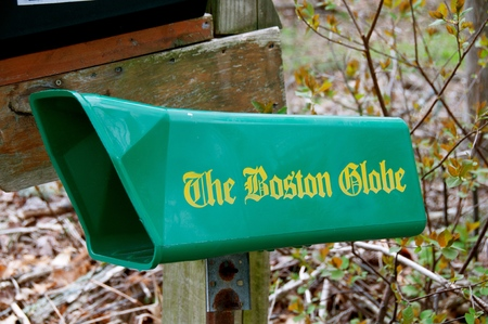 ROWLEY, MASSACHUSETTS, April 28, 2019: The green mailbox collects the daily newspaper The Globe,  an American daily newspaper founded and based in Boston, Massachusetts, since its creation by Charles