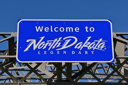 Legendary sign welcome travelers to North Dakota hangs over the entrance of a bridge. Imagens