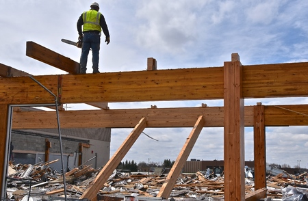 A construction worker  displays balance as he uses a chain saw to cut off wood beams in a demolition of a building.