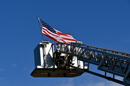The United States flag with no stars is displayed on top of a fire truck extension ladder.