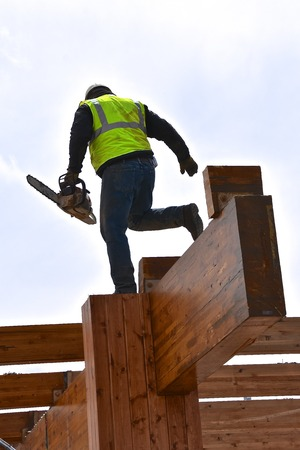 A construction worker  displays balance as he uses a chain saw to cut off wood beams in a demolition of a building. Imagens - 122800592