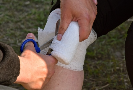 A bandage and first aid is being applied to an injured knee