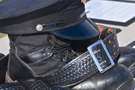 The head gear, belt, and boots of a fallen police officer in the line of duty. Imagens - 122800638