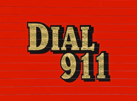 A red Dial 911 sign is on the side of a fired and rescue vehicle